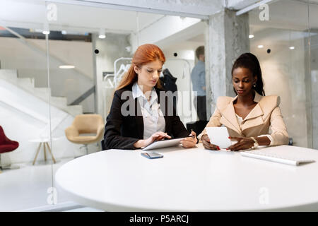 Two attractive businesswomen using technology