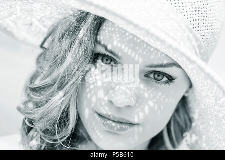 Beauty teenager with hat on head face closeup portrait looking at camera serious fine-art fineart artistic arty - Stock Photo