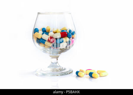 Colorful pills and medication in a glass on white background, health and medication concept - Stock Photo