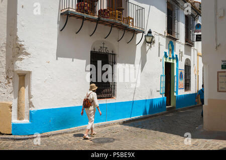 Rear view of a mature, middle aged woman traveler exploring a street in the old town quarter of Cordoba, Andalucia, Spain. - Stock Photo
