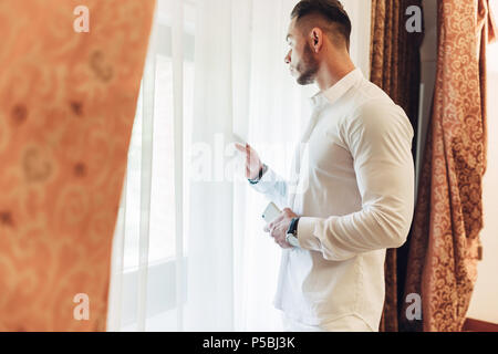 Young Man in White Suit in Hotel Room - Stock Photo
