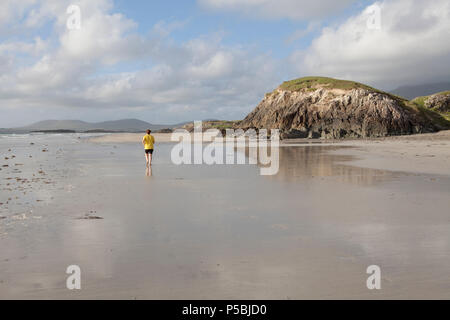 A woman runs along the empty sands of Lettergesh Beach one of many stunning Connemara beaches. County Mayo, Ireland - Stock Photo