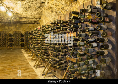 Many old wine bottles stacked on wooden racks in a cellar - Stock Photo