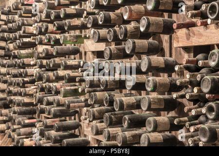 Many old wine bottles stacked on wooden racks - Stock Photo