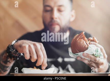 Young bearded man eating burger and french fries. - Stock Photo