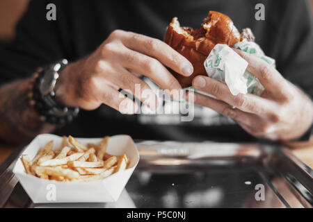 Young bearded man eating burger and french fries close up. - Stock Photo
