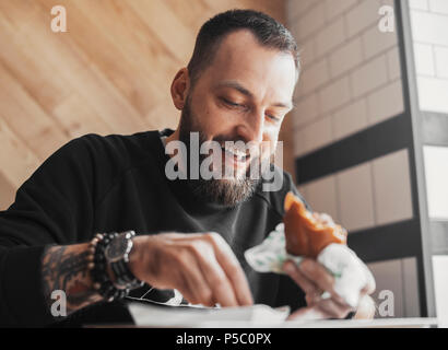 Young bearded man eating burger and smiling close up. - Stock Photo