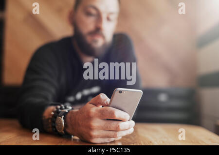 Young tattooed man holding mobile phone in right hand close up. - Stock Photo