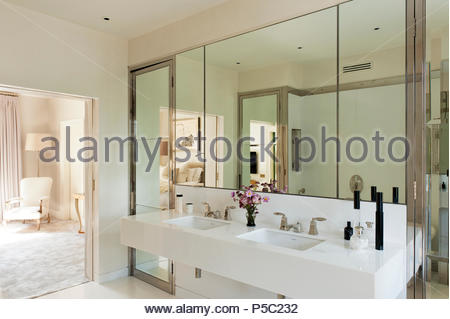 White sink in mirrored bathroom - Stock Photo