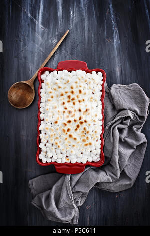 Sweet Potato Casserole baked with mini marshmallows ready for Thanksgiving Day. A piece missing from corner. Shot from above. - Stock Photo