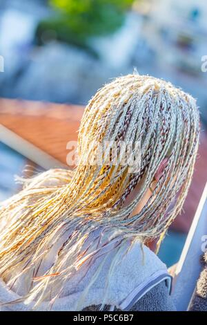 Long braided  elaborate worked on hair against sunlight MR - Stock Photo