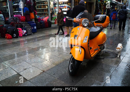 Istanbul, Turkey - December 31, 2016: Details of a wet orange Piaggio Vespa S in a rainy day at Istanbul Kadikoy. Some people are walking around. - Stock Photo