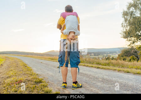 Father carrying his daughter piggyback in summer - Stock Photo