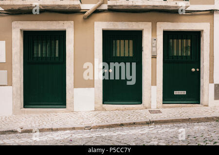Simple wooden entrance doors are arranged in a row - Stock Photo