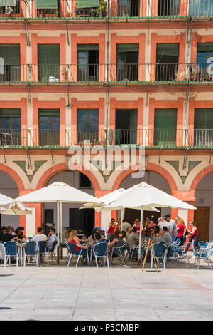 Cordoba cafe bar, tourists relax at a cafe terrace in the 17th Century Plaza de la Corredera in Cordoba on a summer afternoon, Andalucia, Spain. - Stock Photo