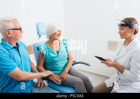 ENT doctor in discussion with mature patients at medical clinic - Stock Photo