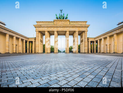 Famous Brandenburger Tor (Brandenburg Gate), one of the best-known landmarks and national symbols of Germany, in beautiful golden morning light at sun - Stock Photo
