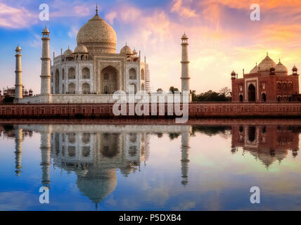 Taj Mahal Agra India with east gate at sunset with moody sky. - Stock Photo