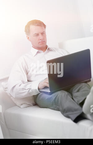 businessman working on laptop while sitting in a hotel room - Stock Photo