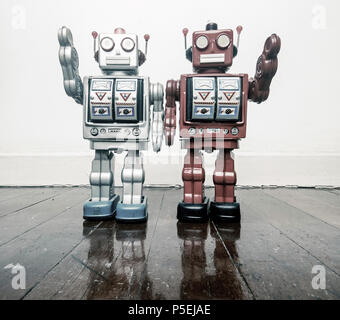 two vintage robots say hi  on a wooden floor toned image - Stock Photo