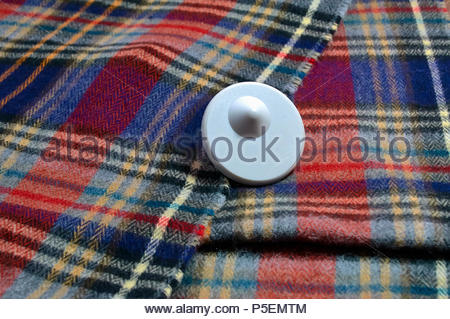 A plastic anti theft security tag on a tartan scarf to stop shoplifting from retail shops - Stock Photo