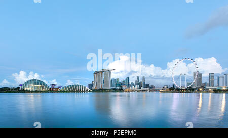 Sun rising over the downtown skyline of Singapore as viewed from across the water from The Garden East. Singapore. - Stock Photo