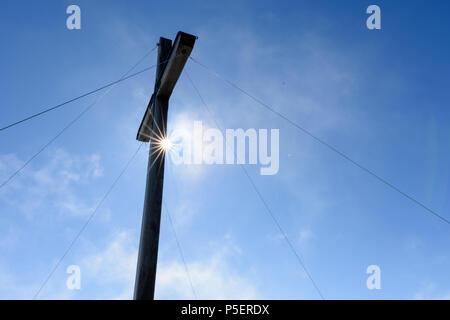 Summit cross with sun star in front of blue sky - Stock Photo