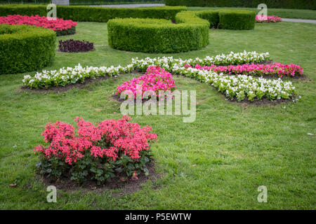 Flowerbed with various flowers, hedges and green meadow in Volksgarten, Vienna (Austria) - Stock Photo
