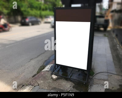 Vertical blank billboard on day city street for mockup design. Street board mock up on footpath advertising. - Stock Photo