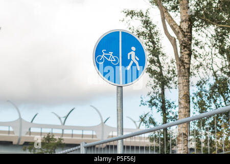 Sign for pedestrians and cyclists near a road in the park. Close up shot.Bicycle and Walking Path Sign with Sky Background.Copy space. Sport outside.Bicycle and pedestrian blue sign, board - Stock Photo