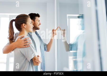 happy couple looking through window at new home - Stock Photo