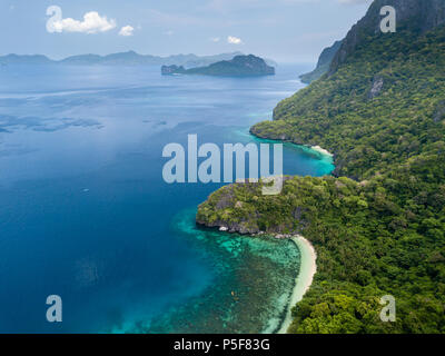 Aerial drone view of a tropical island, surrounding coral reefs, jungle and beaches - Stock Photo