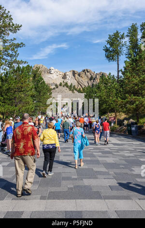 MOUNT RUSHMORE, KEYSTONE, SOUTH DAKOTA, USA - JULY 20, 2017: Visitors walk along the Avenue of Flags with Mount Rushmore in the background - Stock Photo
