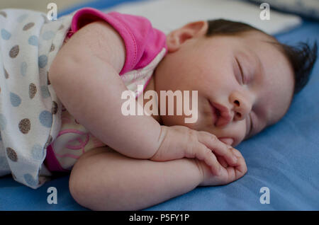 A baby sleeping soundly with her hands folded under her face and her mouth partially open. - Stock Photo