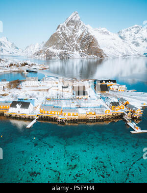 Aerial view of Lofoten winter scenery with traditional fisherman Rorbuer cabins and mountain peaks at sunrise, Sakrisoy, village of Reine, Norway - Stock Photo