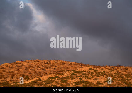 Greek mountain, Golden hour beautiful light with grey clouds, Saronida, Greece. - Stock Photo