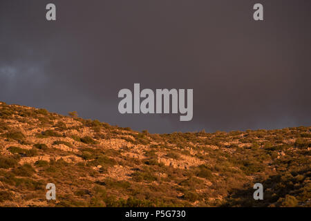 Greek mountain, Golden Hour Beautiful Light with Grey Dramatic Clouds, Saronida, Greece. - Stock Photo
