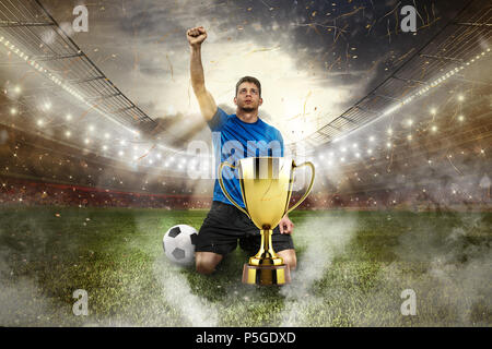 Golden winner's cup in the middle of a stadium with audience - Stock Photo