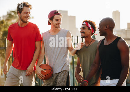 Four cheerful basketball men walking on pavement talking. Men walking back after a game of basketball. - Stock Photo