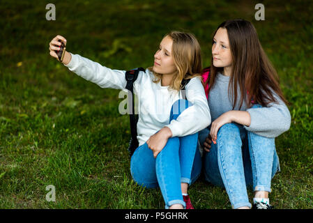 Two teenage girls. In the summer of the city park. They sit on the grass and take photos on smartphone. Behind backpacks. The concept of school friendship. Emotion pose on the phone. - Stock Photo