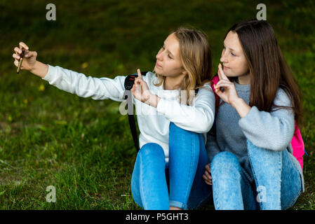 Two teenage girls. In the summer of city park. They sit on the grass and take photos on the smartphone. Behind backpacks. Make a video call over the Internet. Communicates in social networks. - Stock Photo