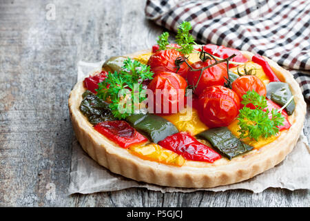 Vegetarian  quiche with colored pepper and cherry tomatoes on wooden table - Stock Photo
