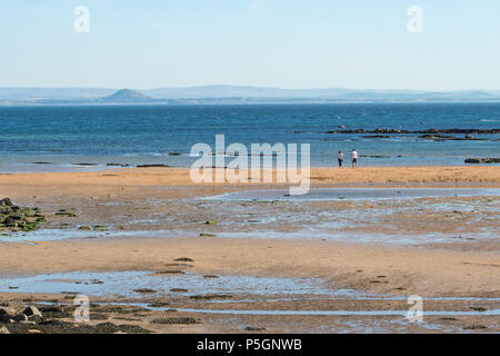 Firth of Forth - couple on Anstruther beach, Fife, looking across the Firth of Forth to North Berwick and the distinctive outline of North Berwick Law - Stock Photo