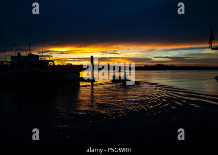 A striking inspirational red coloured cloudy marina sunset seascape over sea water with water reflections.  Captured in Tin Can Bay, Queensland, Austra - Stock Photo