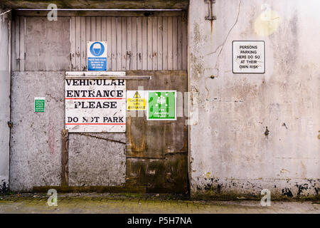 Signs on a wooden doorway saying 'Vehicular entrance.  Please do not park.' and 'Persons parking here do so at their own risk'. - Stock Photo
