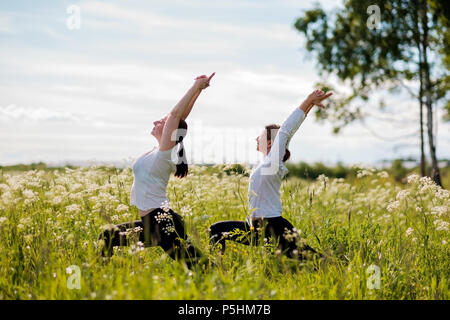 Young two women practicing yoga outdoor in park. - Stock Photo