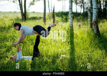 two woman on field doing fitness yoga exercise together - Stock Photo