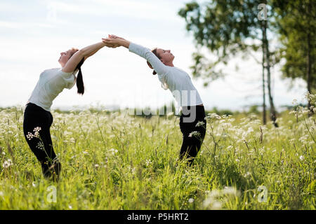Two women le doing yoga exercises, standing bending to each other at outdoors in nature park. - Stock Photo