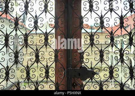 View from a window at the Our Lady of Loreto Church in Prague. Intricate wrought iron screens open to exterior courtyard view - Stock Photo