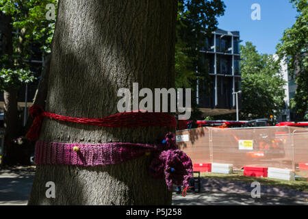 London, UK. 26th June 2018. Works continue in Euston Square Gardens involving the felling of mature London Plane, Red Oak, Common Lime, Common Whitebeam and Wild Service trees to make way for temporary sites for construction vehicles and a displaced taxi rank as part of preparations for the HS2 rail line. Local residents have attached knitted bands to the trees in protest against their planned felling. Credit: Mark Kerrison/Alamy Live News